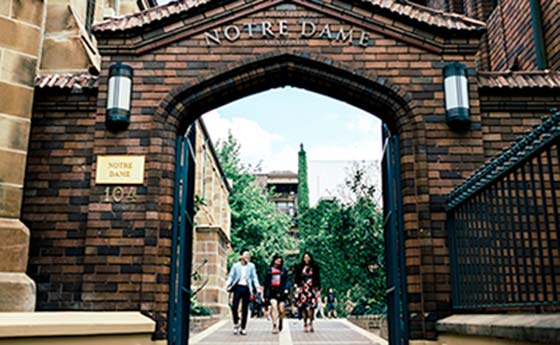 students walking under an arch at University of Notre Dame Australia (UND)